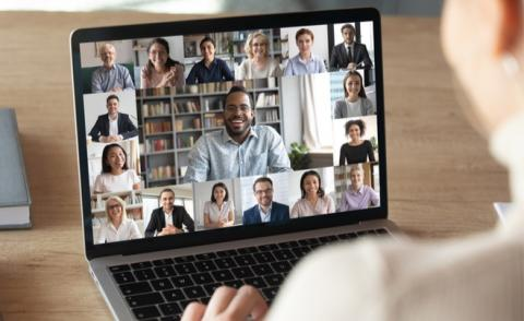 Back view of female employee on video call with coworkers on laptop at home © fizkes - Shutterstock