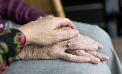 Image of an older person holding hands