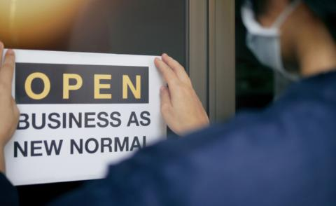 Business owner in mask places Open business as new normal sign on door © Chansom Pantip - shutterstock