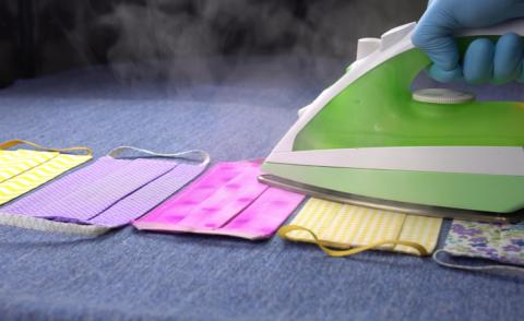 Sterilization of colorful cloth face masks for COVID-19 with steam iron © Fevziie - shutterstock