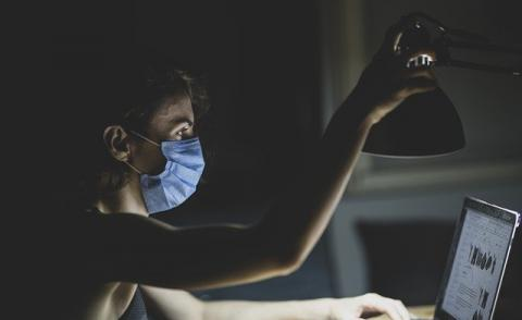 Image of someone working with a mask on during COVID-19