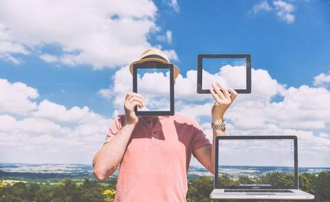 Image of a man holding a tablet standing in front of some clouds