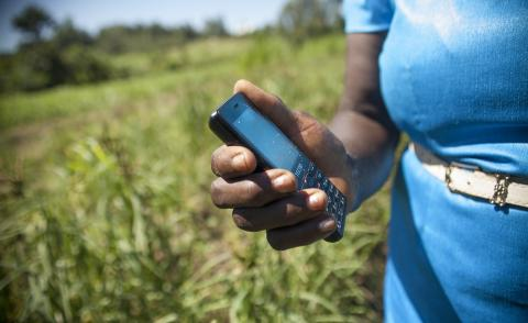 Image of a farmer holding a mobile phone