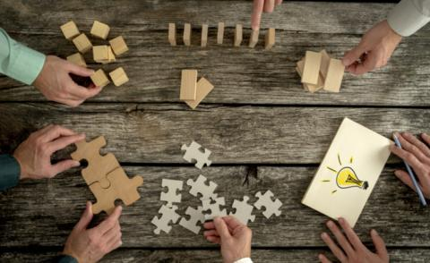 Planning business strategy while holding puzzle pieces, creating ideas with light bulb drawn on paper and rearranging wooden blocks © Gajus - Shutterstock
