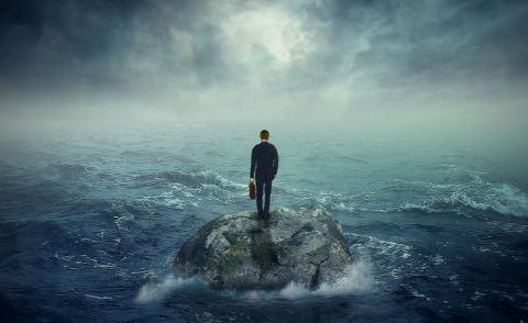 Businessman standing on island surrounded by stormy ocean © ESB Professional