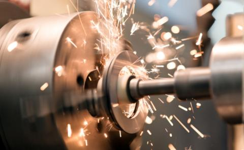 Manufacturing - metalworking on lathe grinder with flying sparks © Vadim Ratnikov - shutterstock